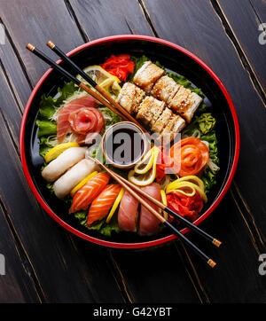 Sushi Set nigiri, rolls and sashimi served in traditional Japan black Sushioke round plate - Stock Photo