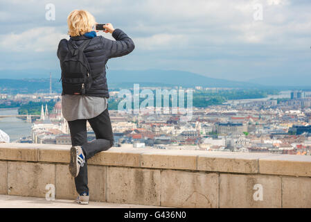 Woman solo traveler, a female tourist photographs the centre of Budapest from the top of Gellert-hegy Hill on the - Stock Photo