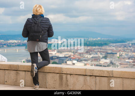 A young female tourist wearing a backpack surveys the centre of Budapest from the top of Gellert-hegy (hill) on - Stock Photo