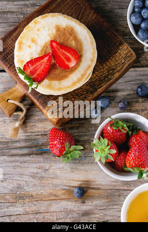 Pancakes with strawberries and blueberries, bowls of honey and fresh berries over old wooden background. Breakfast - Stock Photo