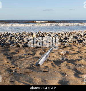 A message in a bottle washed up on a beach - Stock Photo