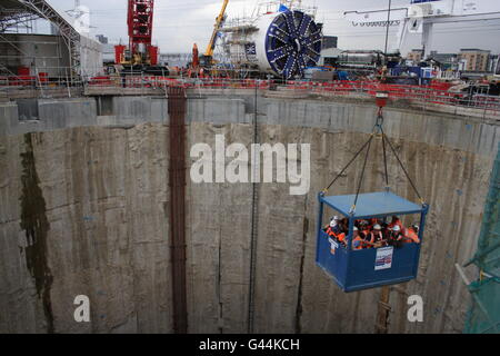 Crossrail workers lowered into a shaft in East London with TBM in the background - Stock Photo