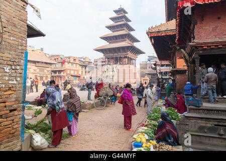 Bhaktapur, Nepal - December 5, 2014: People buying and selling goods at the market on Taumadhi Square. - Stock Photo
