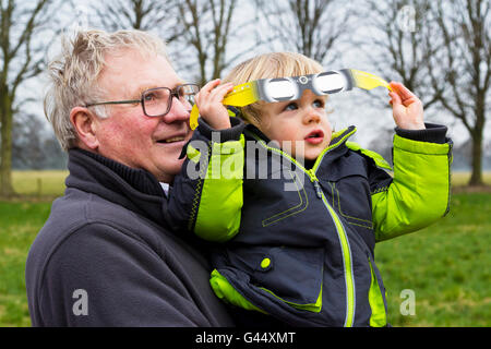 Grandfather holding his grandson whilst watching the partial solar eclipse (Derbyshire, 20th March 2015, UK) - Stock Photo