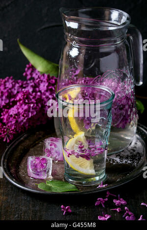 Glass and pitcher of lilac lemonade water  with lemon, ice cubes with lilac flowers and lilac branch on vintage - Stock Photo