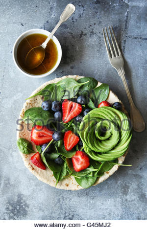 Salad with spinach,berries and avocado rose with honey mustard dressing.Top view - Stock Photo
