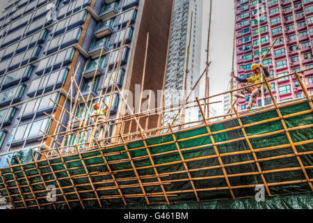 Hong Kong - March 31, 2015: Two construction workers building a bamboo scaffolding on a construction site in Hong - Stock Photo
