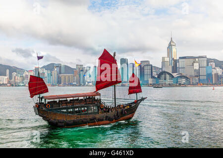 HDR rendering of a typical Chinese junk ship with red sails on Victoria Harbor in Tsim Sha Tsui, Hong Kong. The - Stock Photo