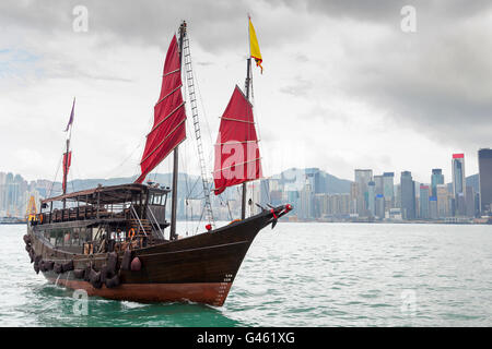 A Chinese junk ship with red sails on Victoria Harbor in Tsim Sha Tsui, Kowloon, with Hong Kong's downtown financial - Stock Photo