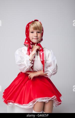 Portrait of brown-eyed girl posing in folk costume - Stock Photo
