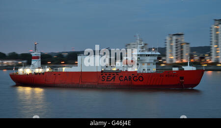 Palletized cargo carrier SC Nordic arrives on the river Thames in London after dark to collect a cargo of exports - Stock Photo