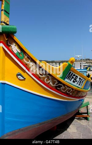 A traditional Maltese fishing boat; locally known as a Luzzu, docked in Marsaxlokk Bay. - Stock Photo