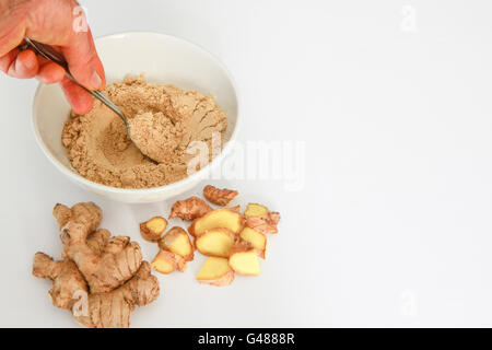 Ginger powder in bowl with metal spoon, hand holding metal spoon. Ginger root, and pieces of ginger root isolated - Stock Photo