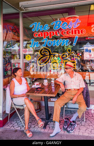Couple have a drink outside at Joe's Cafe, Commercial Drive, Vancouver, British Columbia, Canada - Stock Photo