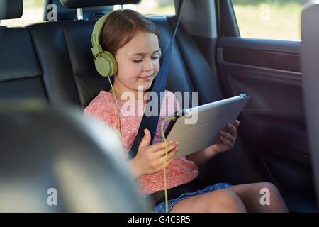 MODEL RELEASED. Girl in the back seat of the car wearing headphones, watching a movie. - Stock Photo