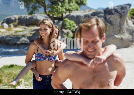 MODEL RELEASED. Parents giving children piggy backs. - Stock Photo