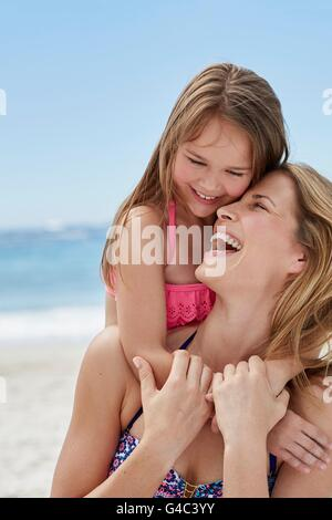 MODEL RELEASED. Mother and daughter laughing on the beach. - Stock Photo