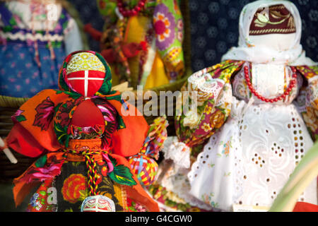 Traditional Russian rag doll at Slavic culture fair. Handmade art textile faceless toy girl souvenir market - Stock Photo