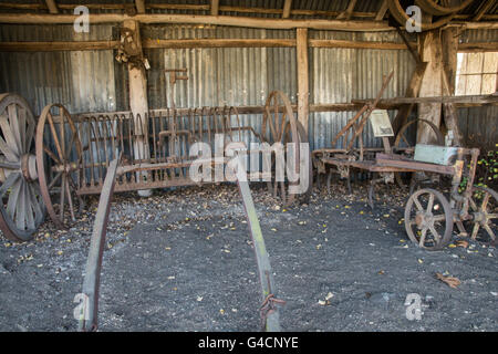 Old Horse Drawn Farm Implements in an old Barn - Stock Photo