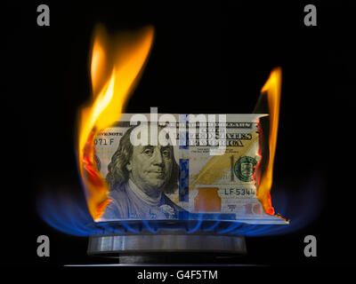 Aflame dollar bill. One hundred dollar bill on fire in gas burner flame. Gas burner burning 100 dollar bill on black - Stock Photo