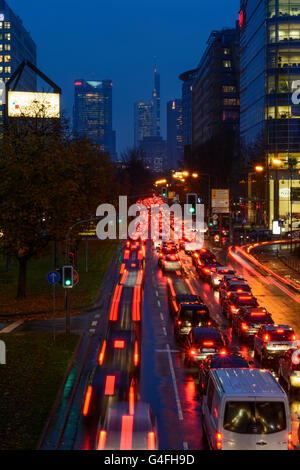 Theodor - Heuss-Allee with cars in traffic jam , night and rain with a view to the town center with the Commerzbank - Stock Photo