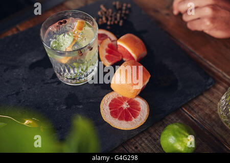 Close up image of freshly prepared cocktail drink with grapefruit slices on table. - Stock Photo