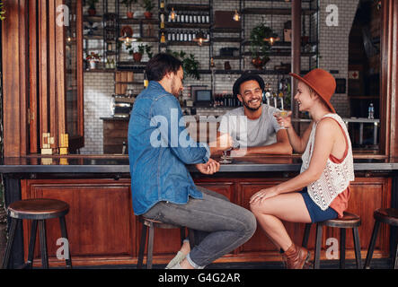 Portrait of three young friends smiling and sitting in a cafe having drinks together. Young men and woman meeting - Stock Photo
