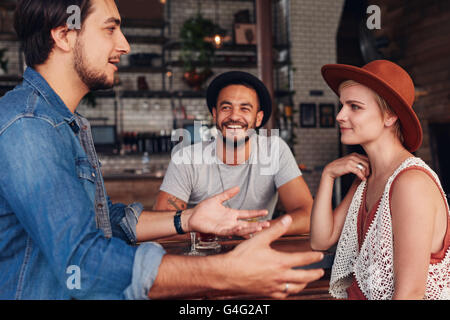 Group of young friends hanging out at a cafe. Young men and women sitting together and talking in a coffee shop. - Stock Photo