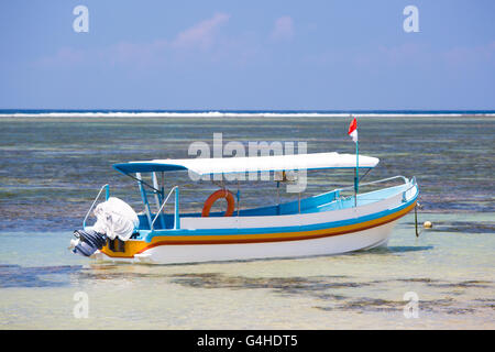 A Balinese fishing boat moored on a Sanur beach in Bali, Indonesia - Stock Photo