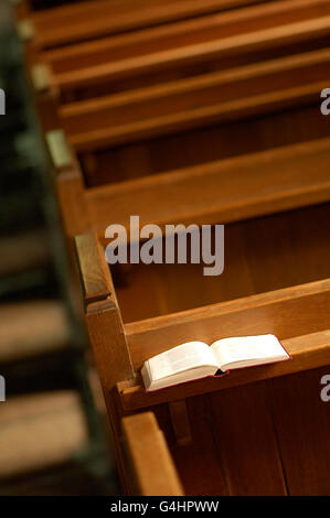Book of Prayer resting on shelf of wooden Pews - Stock Photo