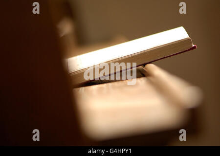 Book of Prayer resting on wooden pew - Stock Photo