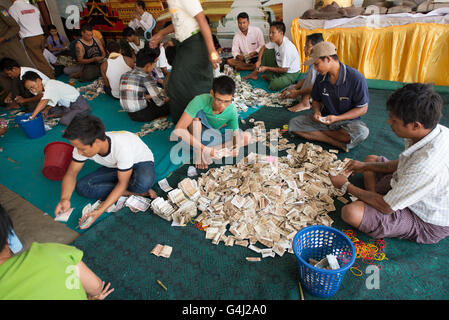 People counting the money alms collecting, Shwezigon Pagoda, Nyanung-U, Mandalay Region, Myanmar - Stock Photo