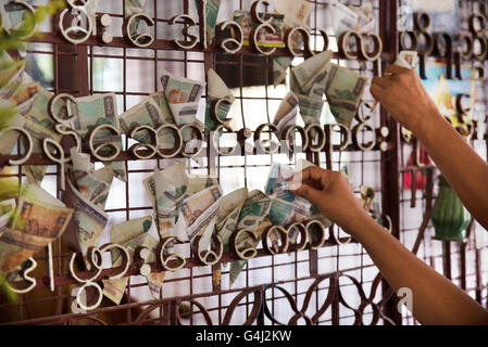People putting money on the grating of Shwezigon Pagoda, Nyanung-U, Mandalay Region, Myanmar - Stock Photo