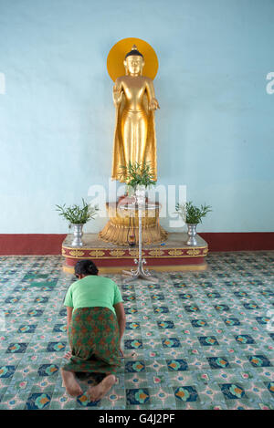 A believer bowing in front of a standing Buddha statue, Shwezigon Pagoda, Nyanung-U, Mandalay Region, Myanmar - Stock Photo
