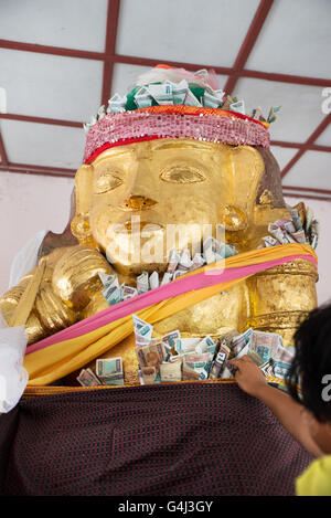 Believers putting money on gilded statues of Nat spirits, Shwezigon Pagoda, Nyanung-U, Mandalay Region, Myanmar - Stock Photo