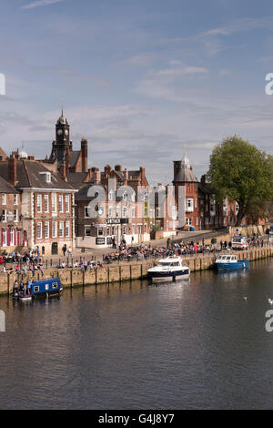 People drinking outside riverside pubs and watching boats on the River Ouse  - King's Staith, York, North Yorkshire, - Stock Photo