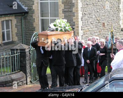 Pall bearers carry the coffin of David Powell, 50, killed in a colliery disaster at Gleision Colliery, near Pontardawe, South Wales, along with his friends and fellow workers Philip Hill, 44, Garry Jenkins, 39 and Charles Breslin, 62, followed by his daughter Charlene (surname not given) and widow Lynette Powell (right) during his funeral service St David's Church in Ystalyfera, South Wales.