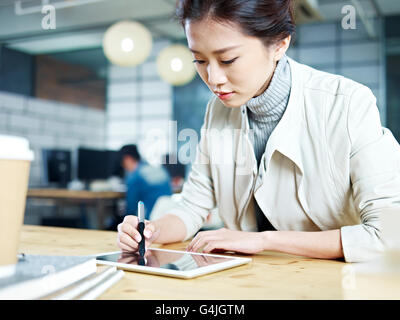 young asian designer working in studio using digital drawing pen and tablet. - Stock Photo