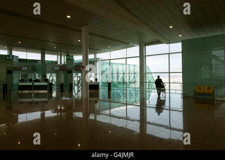Flight delays. Business traveler silhouetted against the departure gate window, waits to board at Barcelona Airport, - Stock Photo
