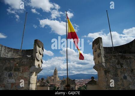 Spanish Flag flying over Segovia castle against backdrop of cloudy sky - Stock Photo