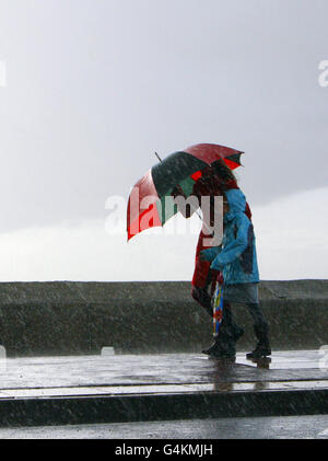 Walkers shelter under umbrellas as they stroll on the seafront in Southsea, Hampshire. - Stock Photo