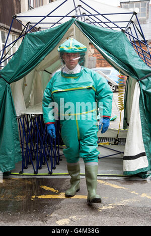 Man wearing a decontamination suit walking from a decontamination tent - Stock Photo