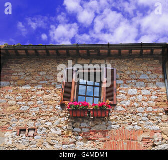 A window with shutters and flowerbox in a medieval stone house. - Stock Photo