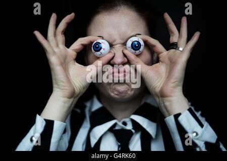 Woman grimacing, artificial eyes - Stock Photo