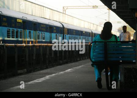 Woman waiting for the train on a bench, Trivandrum, Kerala, India - Stock Photo