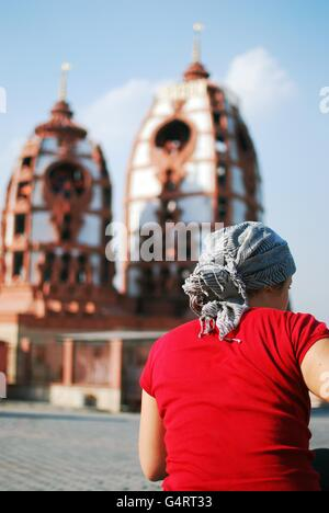 Woman sitting by the Iskcon temple, New Delhi, India - Stock Photo