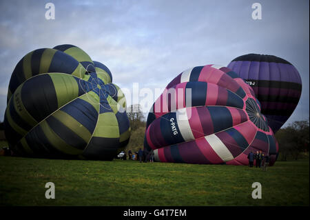Photo. Balloons lay semi-inflated on the ground as crews inflate their hot air balloons with a petrol driven fan, before lighting the propane burners as they prepare for flight at the 40th Annual International Icicle Balloon Meet, on the first full weekend in January and attended by pilots and balloon crews from all over the world, gathering in a field near Savernake Forrest, near Marlborough, to take flight across the Wiltshire countryside.