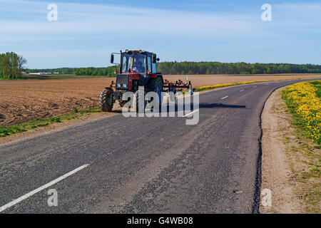 The peasant works at an agricultural field at tractor. Along the road yellow dandelions. - Stock Photo