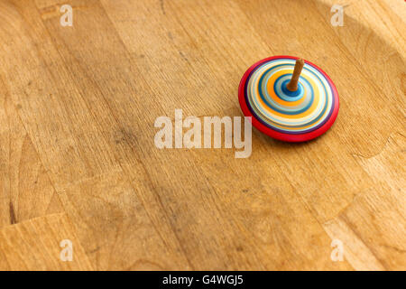 Spinning top. A wooden spinning-top in action on a wooden handmade table. - Stock Photo