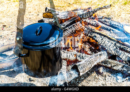 Stockpot, cooking over an open campfire, pea soup with sausages, - Stock Photo